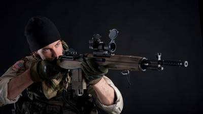 Soldier with rifle against black background.
