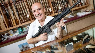 Portrait of a happy mature merchant with rifle in gun shop