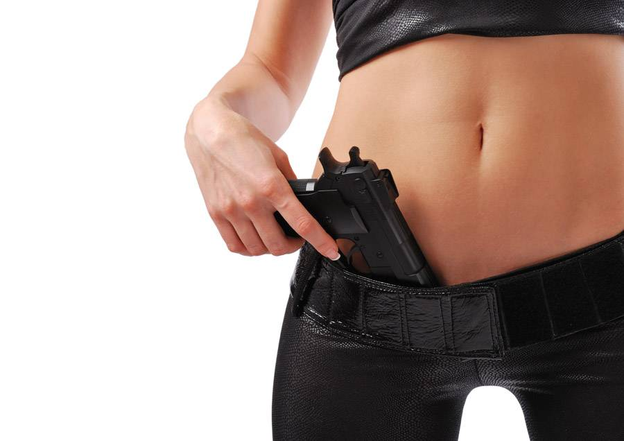 Female hand with pistol and sexy body in black leather.