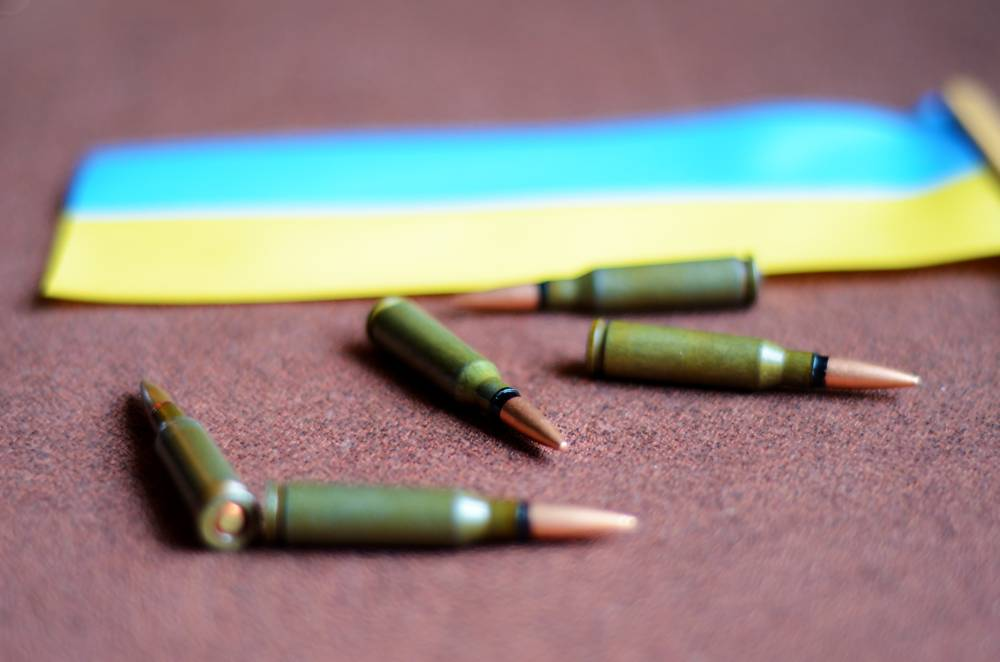Bullets on a background Ukrainian flag (war in Ukraine, victims