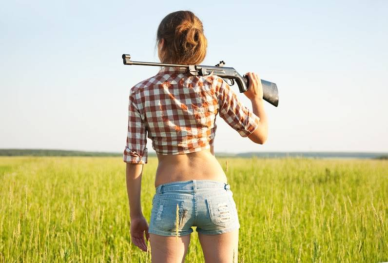young girl with air rifle against field