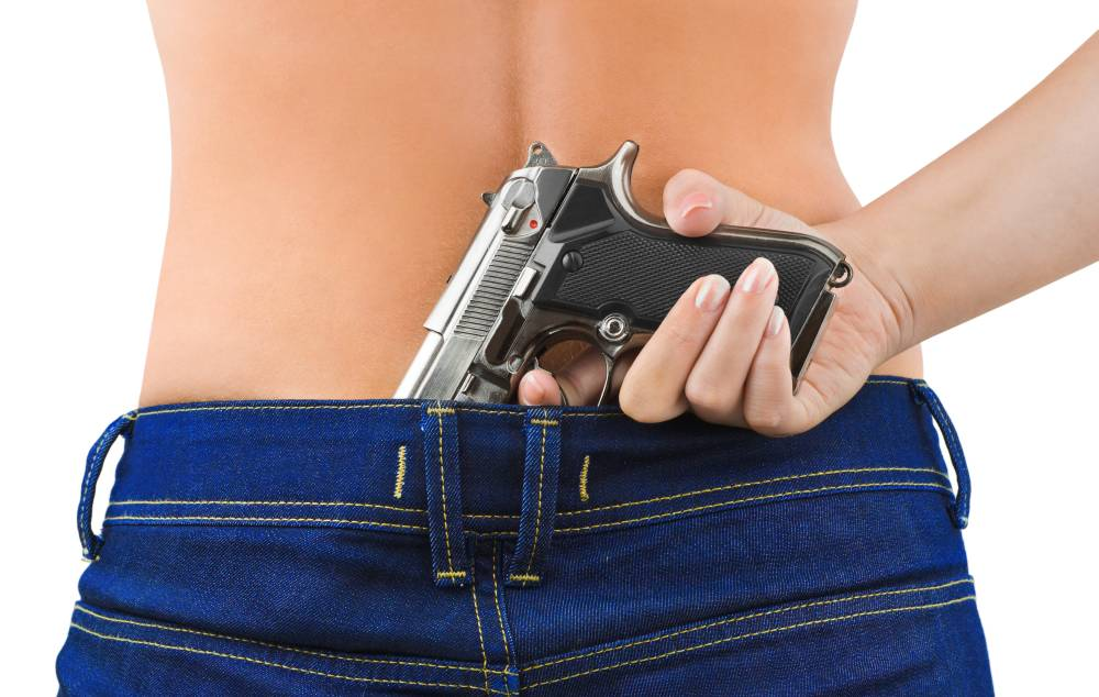 Woman in jeans and gun isolated on white background