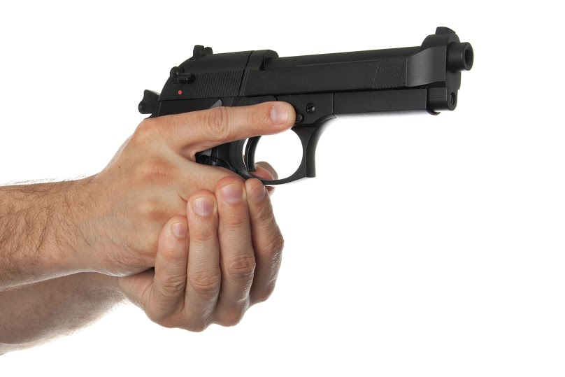 Two hands holding a gun with finger off the trigger on a white background