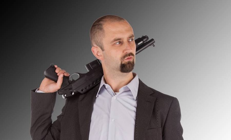 Mafia man is holding a shotgun, isolated on white