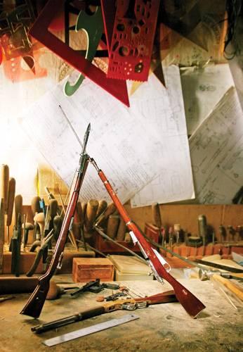Рабочее место мастера-миниатюриста завалено инструментами, чертежами, линейками. Центр композиции составляют, конечно, изделия: крошечная винтовка Мосина скрещена с моделью немецкой Mauser G98. Работы Станислава Архипова