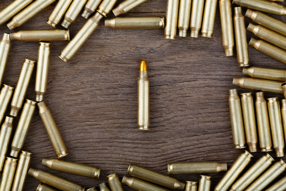 M-16 bullet on wooden table close-up.